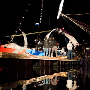 Members of the Arkea Paprec team working on the foils of the Imoca at night